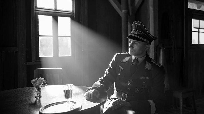 """Fotograma de la película """"The Captain"""" en el que se ve al capitán, progatonista de la historia, vistiendo su uniforme nazi de la segunda guerra mundial, sentado ante una mesa junto a la luz volumétrica que entra por la ventana del barracón, que está tras de si."""