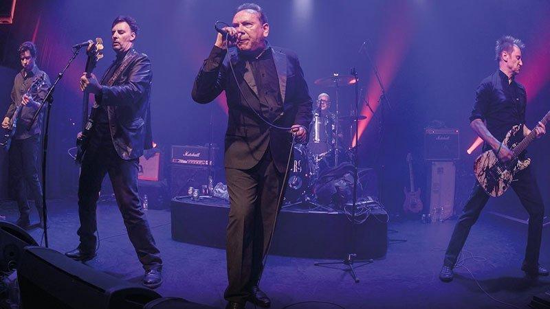 Foto de The Godfathers en directo sobre el escenario en la que se ve en el centro a Peter Coyne empuñando el micro y cantando con su ya clásico traje de mafioso