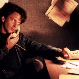 """Fotograma de la película """"Things I never told you"""" en el que se ve a uno de los protagonistas sentado junto a una mesa de oficina hablando por teléfono."""