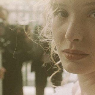 """Fotograma de la película """"Trois couleurs: Blanc"""" en el que se ve en primerísimo plano, a la derecha, la cara de la protanotista, al fondo se puede ver a un hombre grabándola con una cámara sobre un trípode."""