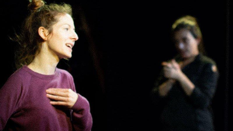 """Foto de una escena de la obra """"Un cuerpo propio"""", de Ximena Vera, en la que se ve a la izquierda del plano a la actriz y dramaturga que dialoga con otra actiz que se aprecia al fondo, desenfocada."""