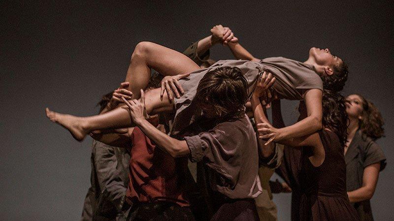 """Foto de una escena de la obra """"Una gran emoción política"""" donde se ve a varios de los actores-bailarines llevando en volandas a la protagonista."""
