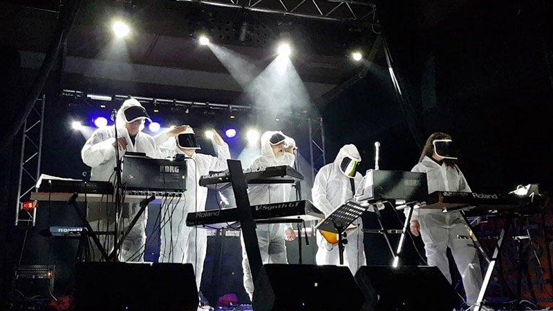 Foto de Aviador Dro en directo en la gira 40 aniversario, donde se ve a sus 5 componentes actuales con sus trajes científicos manipulando todos sus cacharros electrónicos.