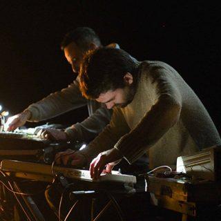 Foto de Balago en directo, donde se ve a sus dos miembros retorciendo sintetizadores y aparatos.