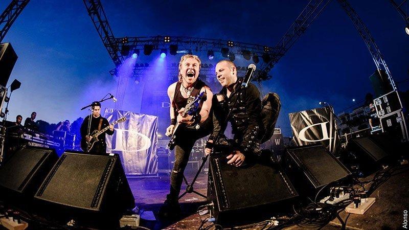 Foto de Dünedain tocando en directo donde se ve a uno de los guitarristas junto al cantante apoyándose en las pantallas de sonido del escenario, de fondo se ve al otro guitarrista y el resto del escenario.