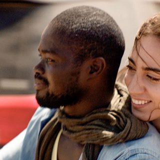 """Fotograma de la película """"El viaje de Marta"""" en el que se ve a los dos protagonista, Marta y su pareja, en un primer plano con el fondo desenfocado, dando la sensación de que viajan en moto por la ciudad."""