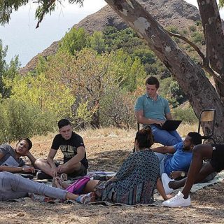 Fotograma de la película L'Atelier en el que se ve a la profesora junto a todos sus alumnos en una clase al aire libre bajo un árbol.