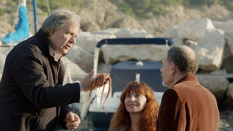 Fotograma de la película La Villa en el que se ve a tres personajes hablando en un puerto, junto a unas embarcaciones, mientras uno de ellos sostiene un pequeño pulpo en su mano.