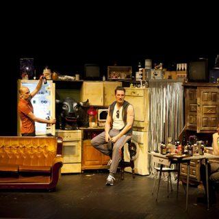 Foto de una escena de Los Mariachis donde se ve a cuatro de sus protagonisttas dialogando en un lúgubre apartamento.