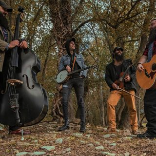 Foto de los cuatro componenntes de Moonshine Wagon posando con sus instrumentos junto a unos árboles en un paisaje muy americano.