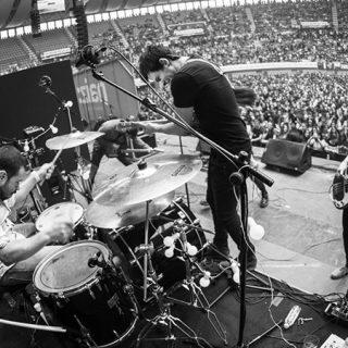 Foto en blanco y negro de Nogen tocando en directo ante un esttadi abarrotado de gente.