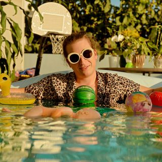 Foto de Chicho, el único componente de Ortiga, metido en una piscina con camisa de leopardo y gafas de sol glamurosas poniendo cara de felicidad y rodeado de juguetes de goma que flotan alrededor suyo.