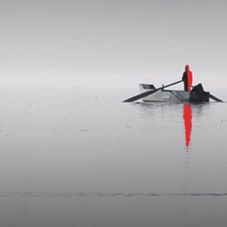 """Detalle de la protada de """"Otro Sentido"""" en el que se ve en la lejanía una barca sobre el agua, con un tripulante de color rojo que proyecta su sombra de color rojo sobre un mar gris, en el primer plano se puede ver a un pato que nada hacia la derecha del plano dejando su estela en el agua."""