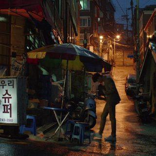Fotograma de la película Gisaengchung (Parásitos) en el que se ve una calle de una ciudad china en perpectiva, en el plano medio un joven, uno de los protagonistas, se acerca a un vendedor ambulante.