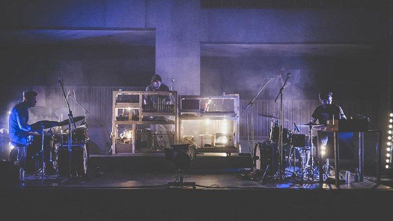 Foto de Slumberland tocando en directo, en el centro se ve a Jochem Baelus, lider de la banda, manejando sus aparatos, y a cada lado una de las baterías que integran el sonido de la banda.