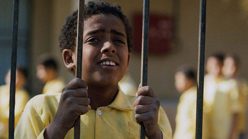 """Fotograma de la película """"Yomeddine"""" en el que se ve a un niño, el protagonista, agarrado a los barrotes de una verja con gesto de tristeza y dolor."""