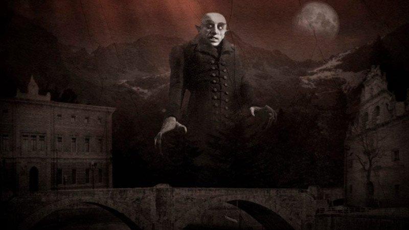 Detalle del cartel de Live Music Zinema en el que se ve a la figura de Nosferatu tras un puente de piedra y rodeado de dos edificios históricos con montes nevados y la luna de fondo.