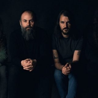 Foto de los cuatro miembros de Adrift sentados con gesto serio mirando a cámara sobre fondo negro.