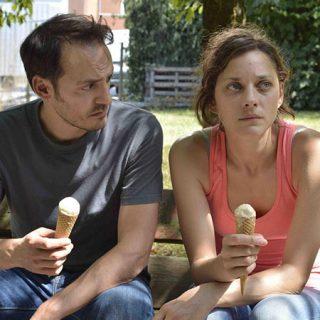 """Fotograma de la película """"Deux jours, une nuit (Dos días, una noche)"""" en ell que se ve a su protagonista, sentada en un banco junto a su marido con cara de preocupación sosteniendo un helado en la mano."""