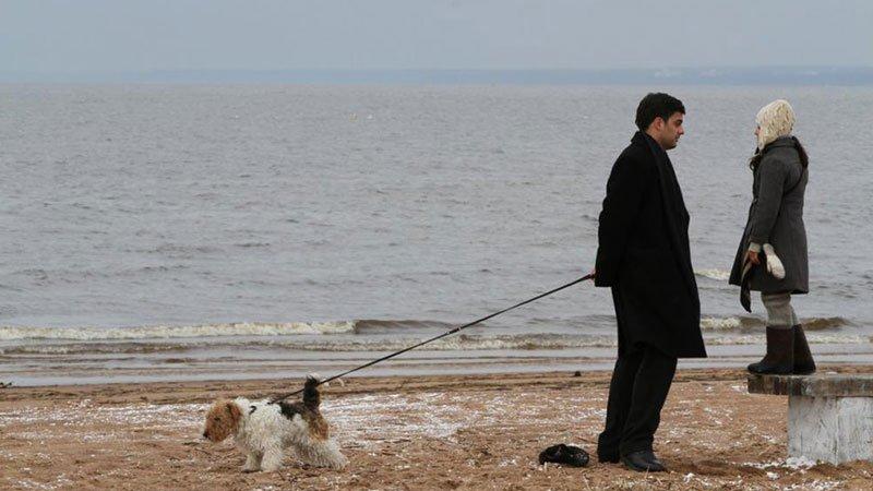 Fotograma de la película Dovlatov en la que se ve a su protagonista hablando con su hija y sosteniendo la correa de su perro, que se ve a sus espaldas.