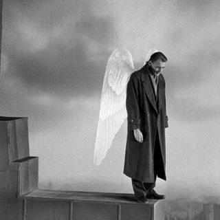 """Fotograma de la película """"El cielo sobre Berlín"""" en el que se ve a su progagonista en la cornisa de un edificio, mirando abajo y con una alas blancas a su espalda."""