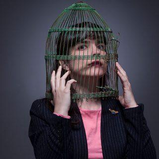 Foto promocional de Elena Setién en la que aparece en plano americano con la cabeza metida en una jaula de pájaros, mientras la sostiene con las manos.