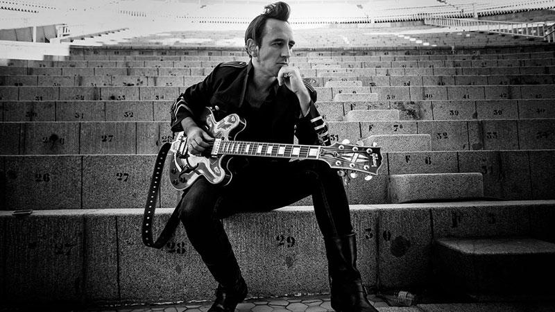 Foto de Igor Paskual sentado en las gradas de un estadio con su guitarra bajo el brazo y gesto pensativo.