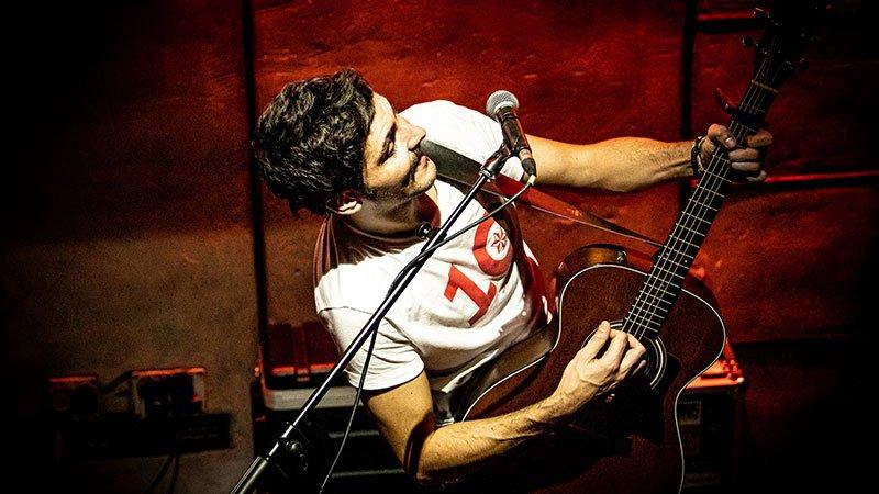 Foto de Indomable tocando en directo, visto desde arriba en un plano contrapicado blandiendo su guitarra junto al micro y sonriendo.