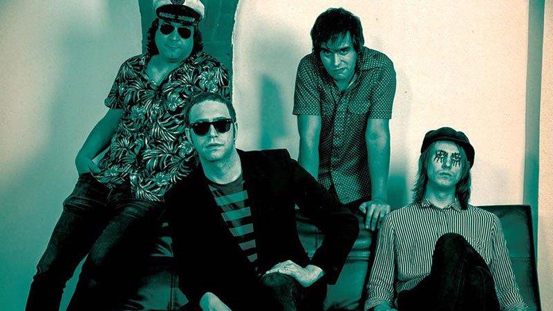 """Foto de los cuatro miembros de """"Kurt Baker Combo"""" posando sentados en un sofá."""