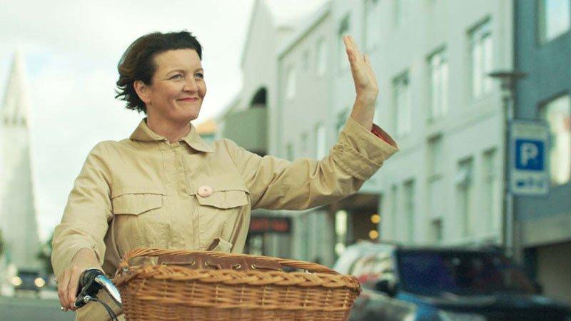 """Fotograma de """"La mujer de la montaña"""" en el que se ve a la progagonista transitando en bici por la calle, sonriente y saludando con su mano izquierda."""