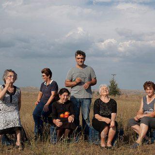 Fotograma del documental donde se ve a varias abuelas del pueblo junto a uno de los jóvenes que emprenden la idea de exportar tomates, todos sentados sobre cajas en medio del campo.