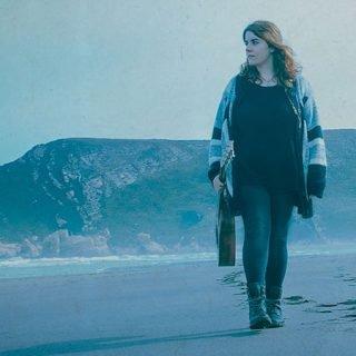 Foto promocional de Noelia Veira en la que se la ve caminando por una playa con su guitarra en la mano entre un ambiente frío con luz azulada.