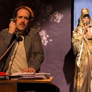 Foto de una escena de la comedia Off, en la que se ve a sus personajes principales, él en primer plano a la izquierda, sentado ante una mesa con el aurícular de un teléfono antiguo puesto a la oreja y cara de sorpendido, ella en el fondo, a la derecha, vesida con manto dorado y sosteniendo un libro.