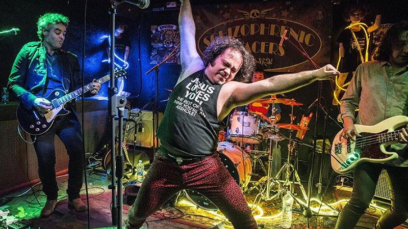 Foto de Schizophrenic Spacers tocando en directo donde se ve a los cuatro miembros de la banda, en el centro el cantante estira brazos y piernas en forma de X con gesto burlón y esforzado.