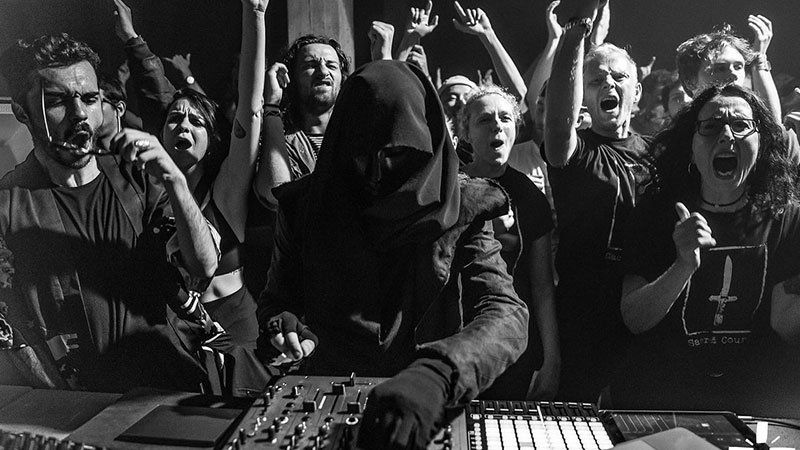 Foto de SNTS en una sesión en directo, con su máscara y s capucha manejando la mesa de mezclas rodeado de gente gozando con la música.