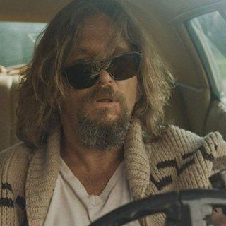 """Fotograma de """"The Big Lebowski"""" en el que se ve a Jeff Bridges dentro de un coche con gafas de sol caídas de un lado y cara de fumao."""