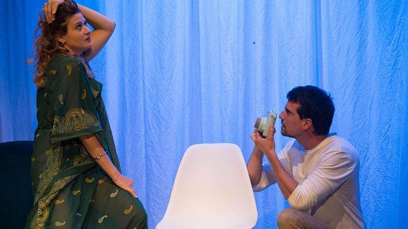 """Un momento de la obra de teatro """"Acreedor@s"""" en el que se ve a dos de sus protagonistas sobre un fondo de tela azul. A la izquierda la chica posa y a la derecha el chico, agachado, sostiene una cámara de fotos."""