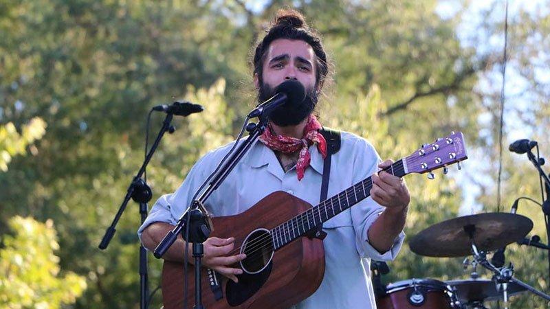 Foto de Anibal tocando en directo al aire libre, con fondo de árboles, sosteniendo su guitarra acústica trás un micrófono.