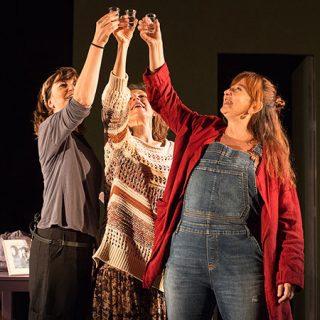"""Foto de una escena de la obra """"Canción para volver a casa"""" en la que se ve a sus tres protagonistas alzando las manos para brindar."""