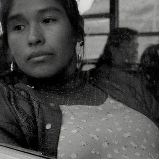 Fotograma de Canción sin nombre en el que se ve a la protagonista sentada en un autobús mirando por la ventanilla con gesto melancólico.
