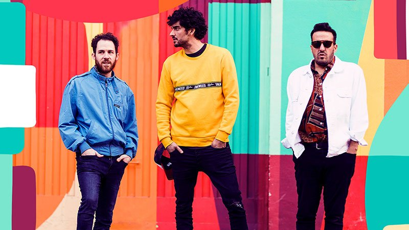 Foto de los tres integrantes de Colectivo Panamera posando con las manos en el bolsillo ante una pared pintada de mil colores.
