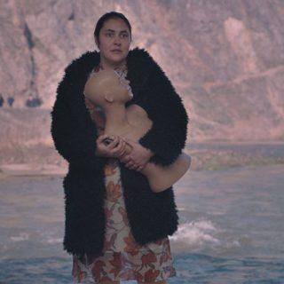 """Fotograma de """"Dios es mujer y se llama Petrunya"""" en el que se ve a su protagonista ante un fondo de mar, de pie con gesto de sorpresa mientras sostiene el busto de un maniquí en las manos."""
