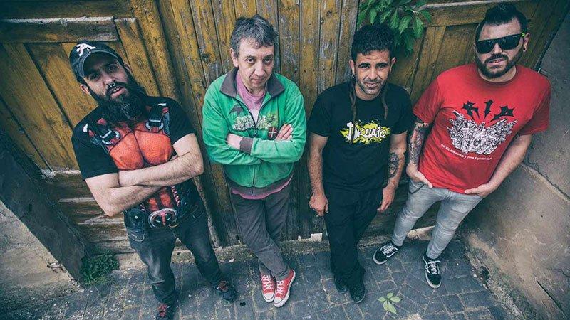 Foto de los cuatro integrantes de Josetxu Piperrak & The Riber Rock Band posando apoyados en una vieja puerta.