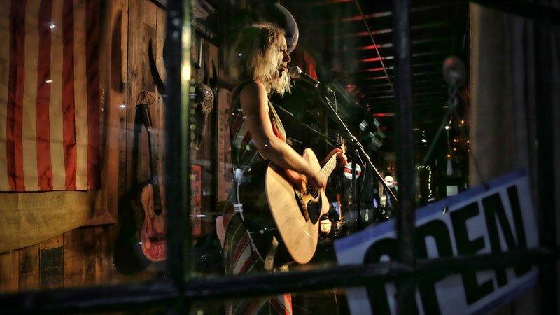 Foto de Juana Everet tocando en un local, guitarra en mano y cantando al micrófono.