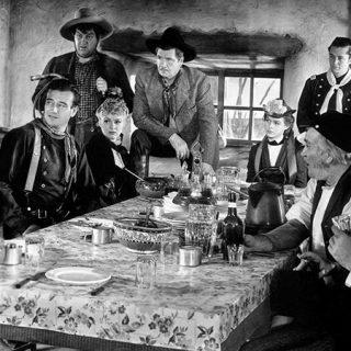 Fotograma de la película Stagecoach en el que se ve a todos sus personajes alrededor de una mesa debatiendo mientras algunos comen.