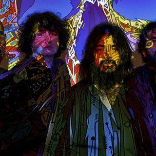 Foto de los cuatro miembros de Los Buges posando bajo una proyección de luces de colores de aspecto psicodélico.
