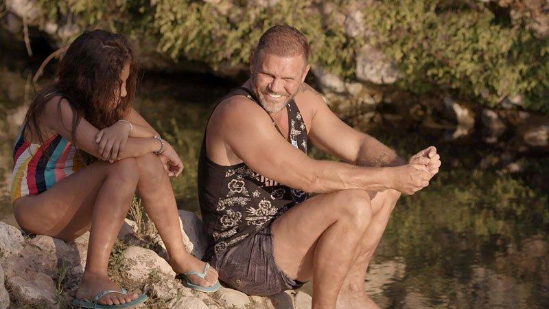 Fotograma de la película Me llamo violeta en el que se ve a Nacho Vidal y a la protagonista sentados junto al río charlando y riendo.