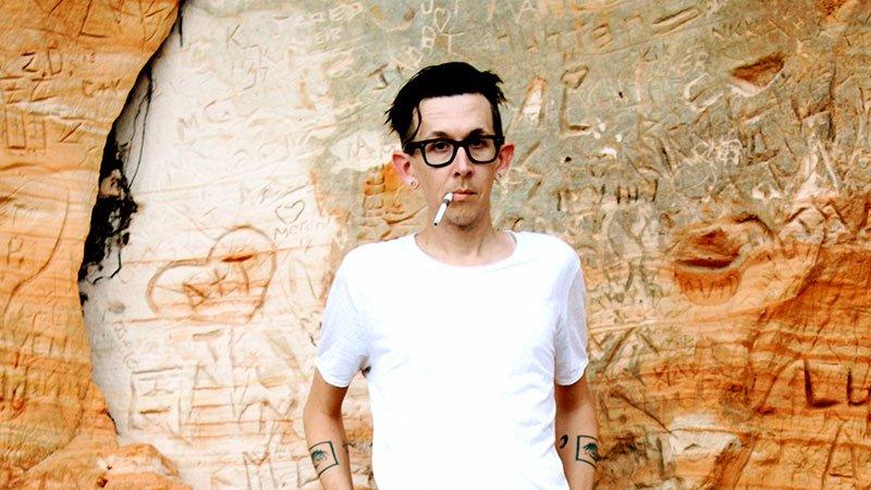 Foto de Micah P. Hinson posando sosteniendo un cigarro con boquilla en su boca de pie ante una pared de piedra con innumerables escritos grabados.