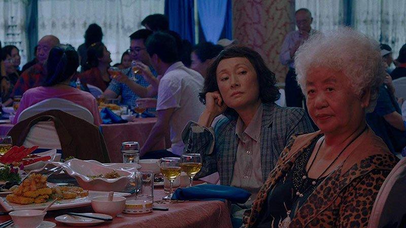 """Fotograma de la película """"The Farewell"""" en el que se ve a su protagonista junto a su hija sentadas ante una mesa en una boda."""