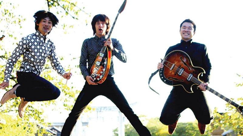 Detalle de la portada de uno de lo álbumes de The Routes, en el que se ve una foto de los tres integrantes saltando con sus instrumentos en la mano con arboles de fondo.